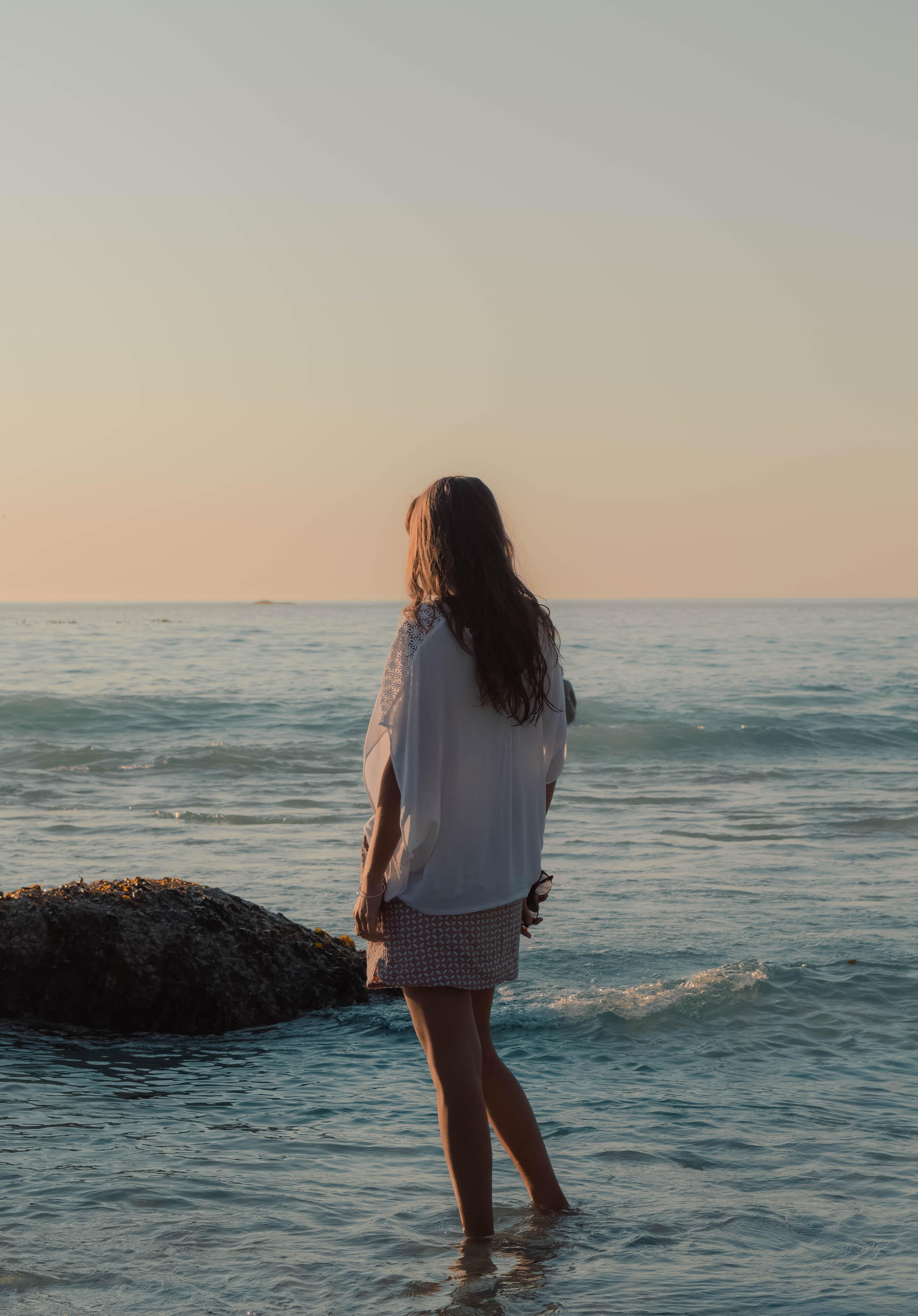 standing woman on water wearing white shirt during daytime