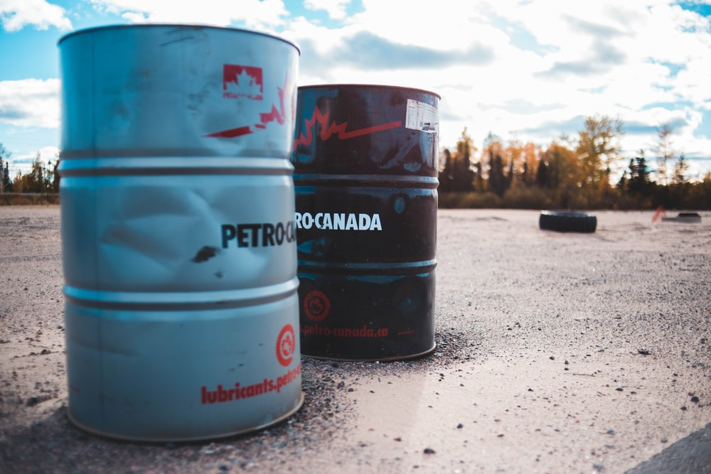 two gray and black metal barrels under cloudy sky\
