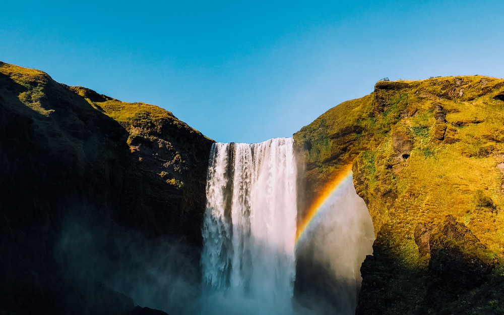waterfalls with rainbow under clear sky at daytime