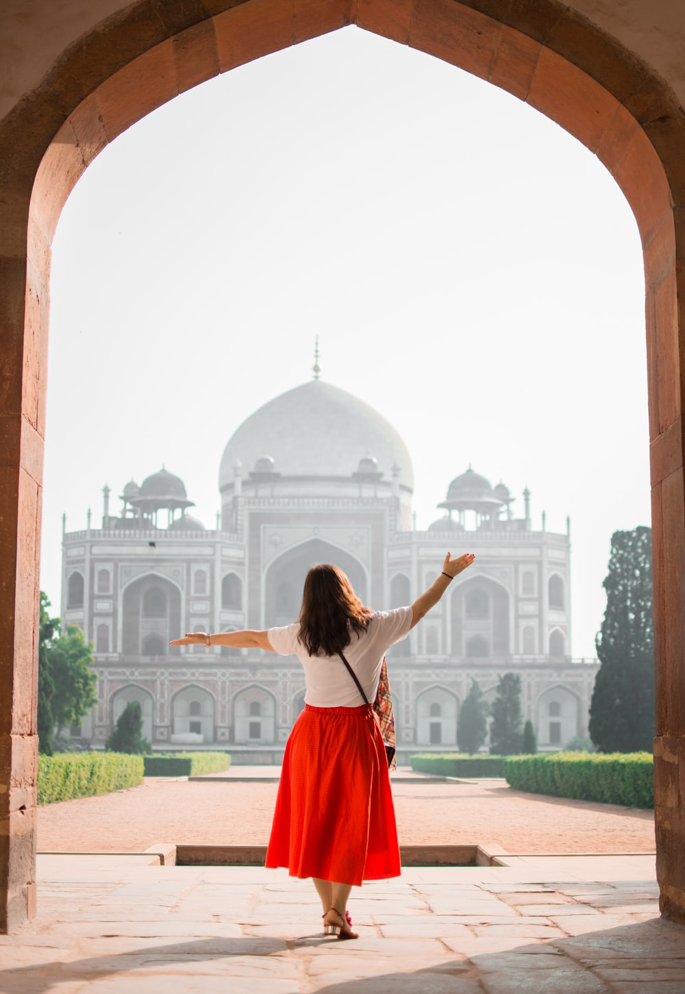woman with hands on air facing mosque