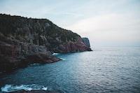 brown rocky mountain next to sea