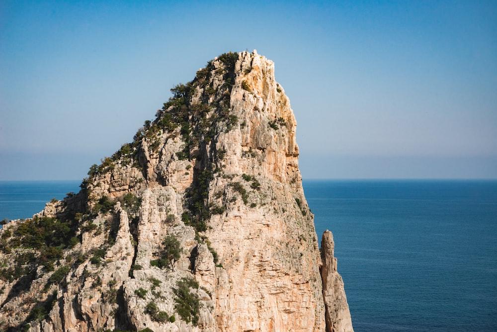 brown rock formation near ocean