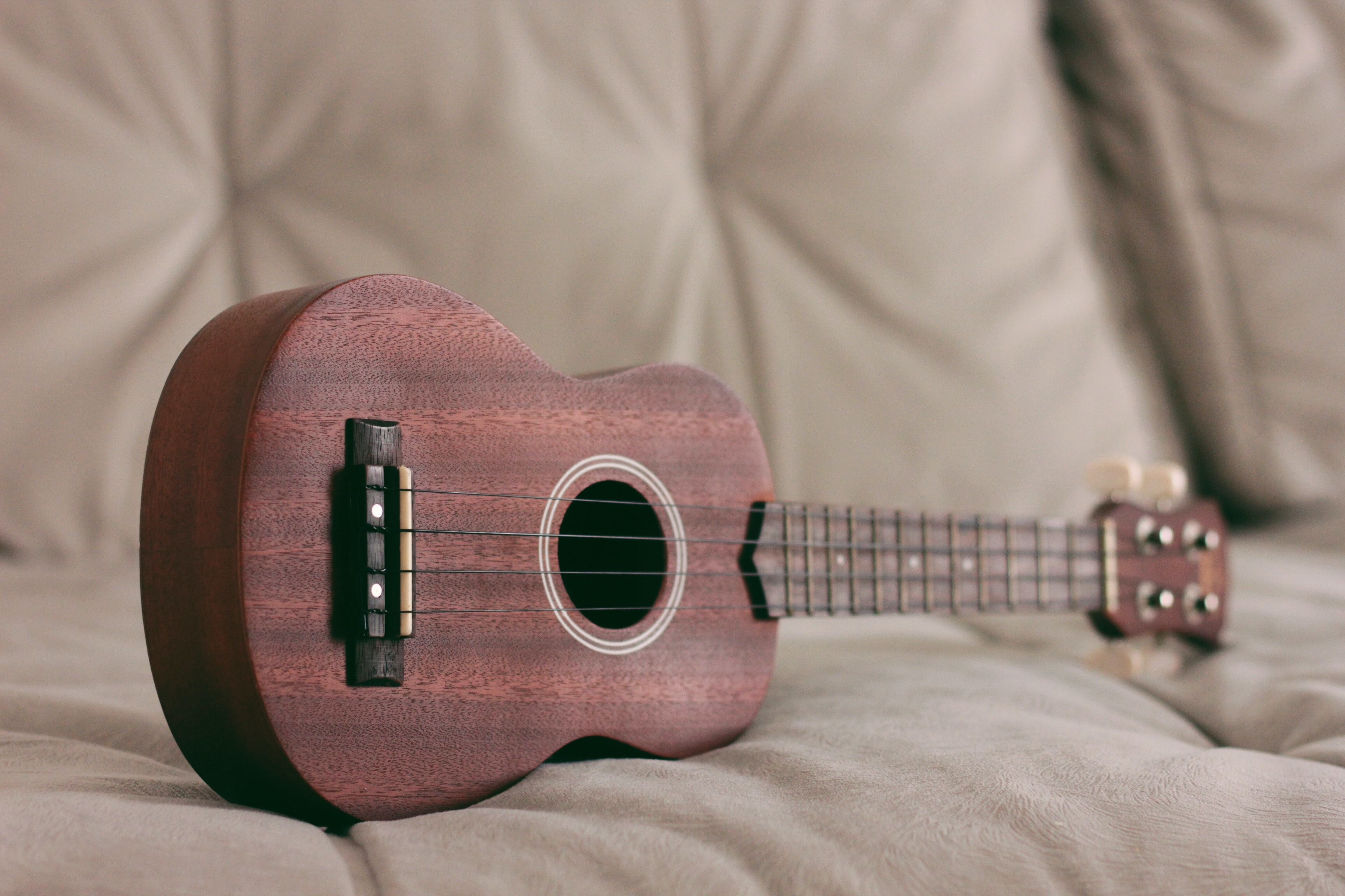 brown ukulele on couch