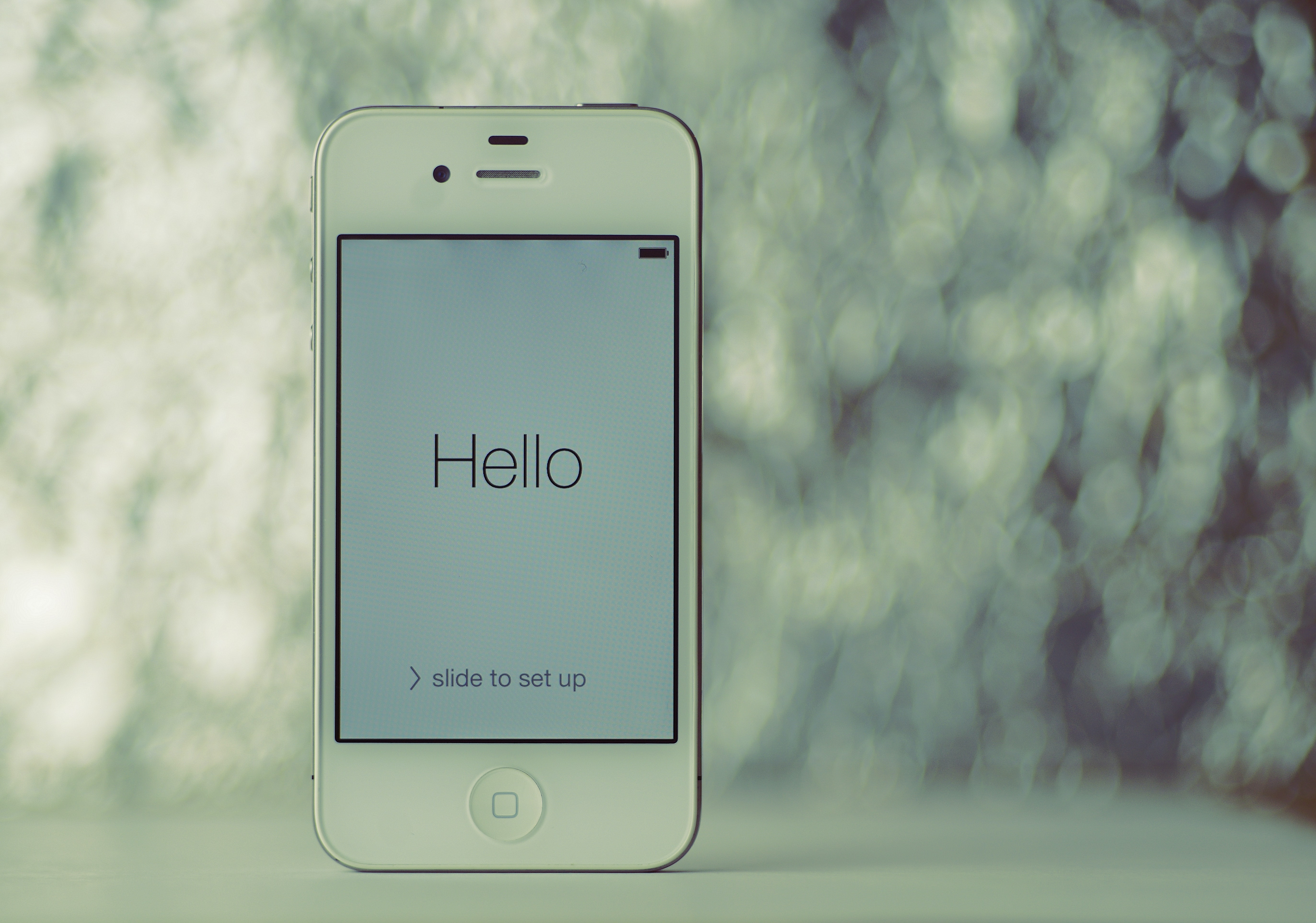 turned-on white iPhone 4 with Hello wallpaper