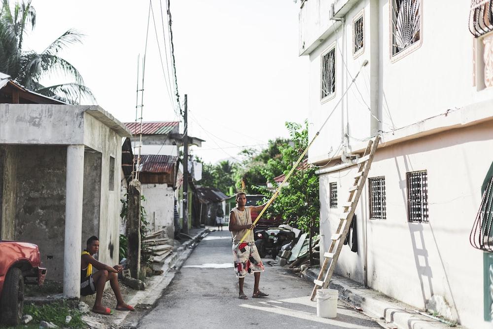 man holding rolling paint brush during daytime