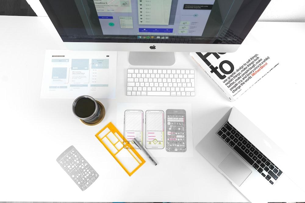 silver MacBook Air on table near iMac