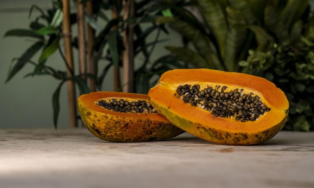 sliced papaya fruits on brown surface