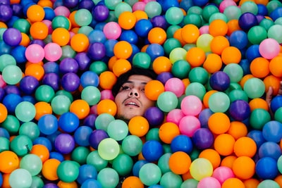 man lying in ball pit conceptual zoom background