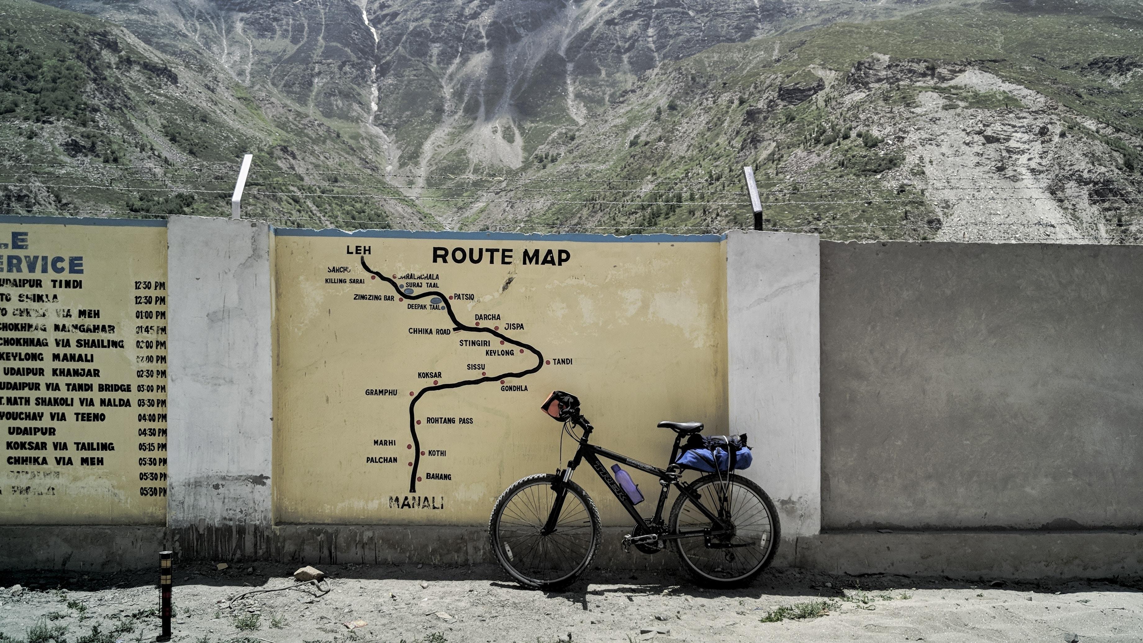 black mountain bike parked beside concrete wall