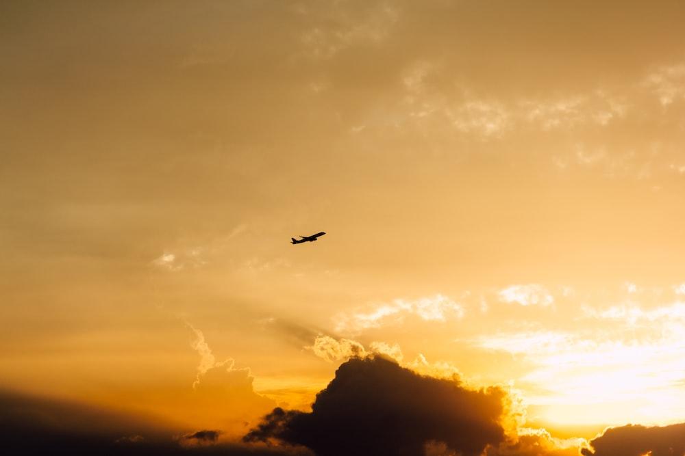 plane over black clouds in orange sky