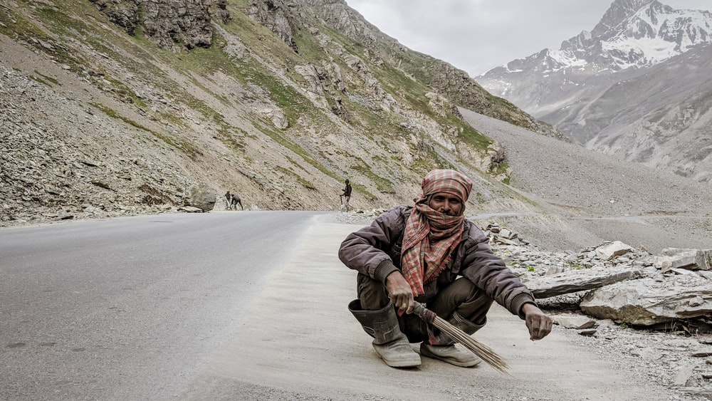 man sitting on gray concrete road holding stick broom