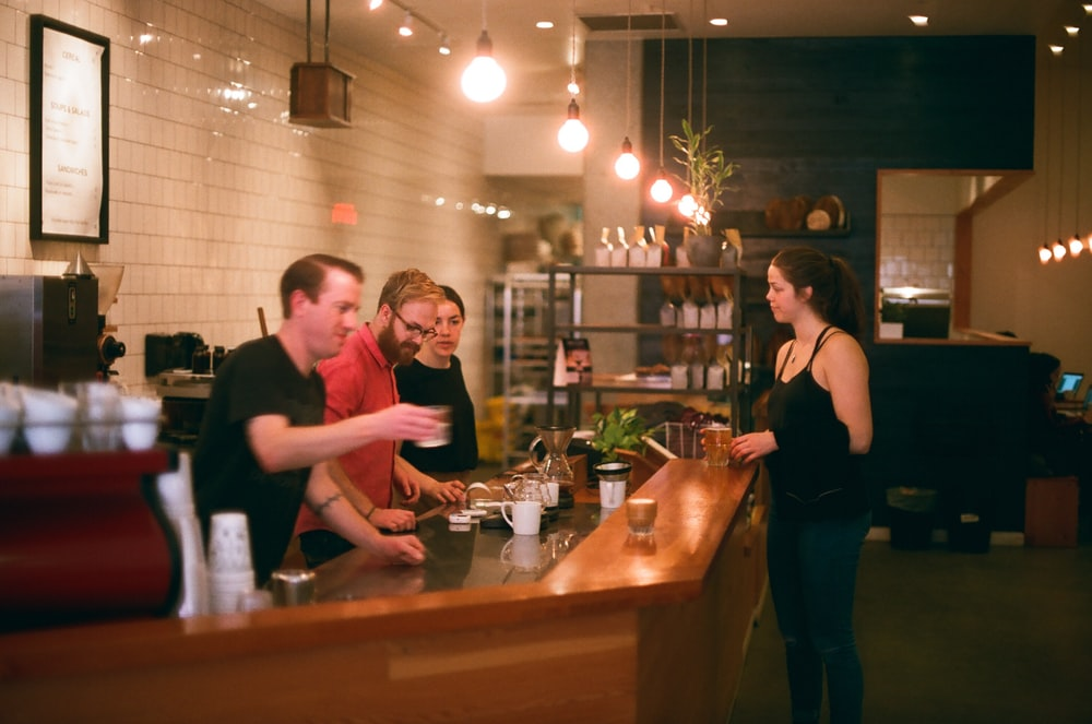 woman in black tank top stands in front of counter with three men inside