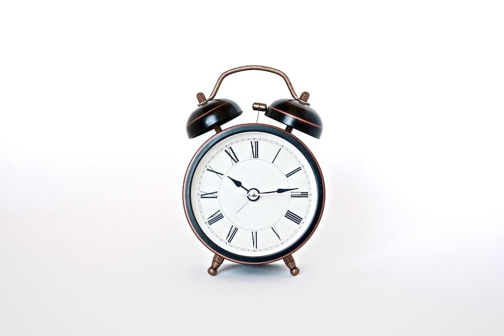 round black and white analog alarm clock