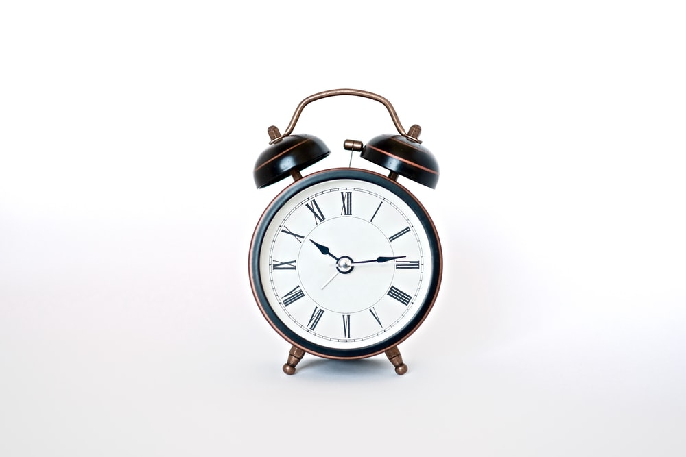 round black and white analog alarm clock