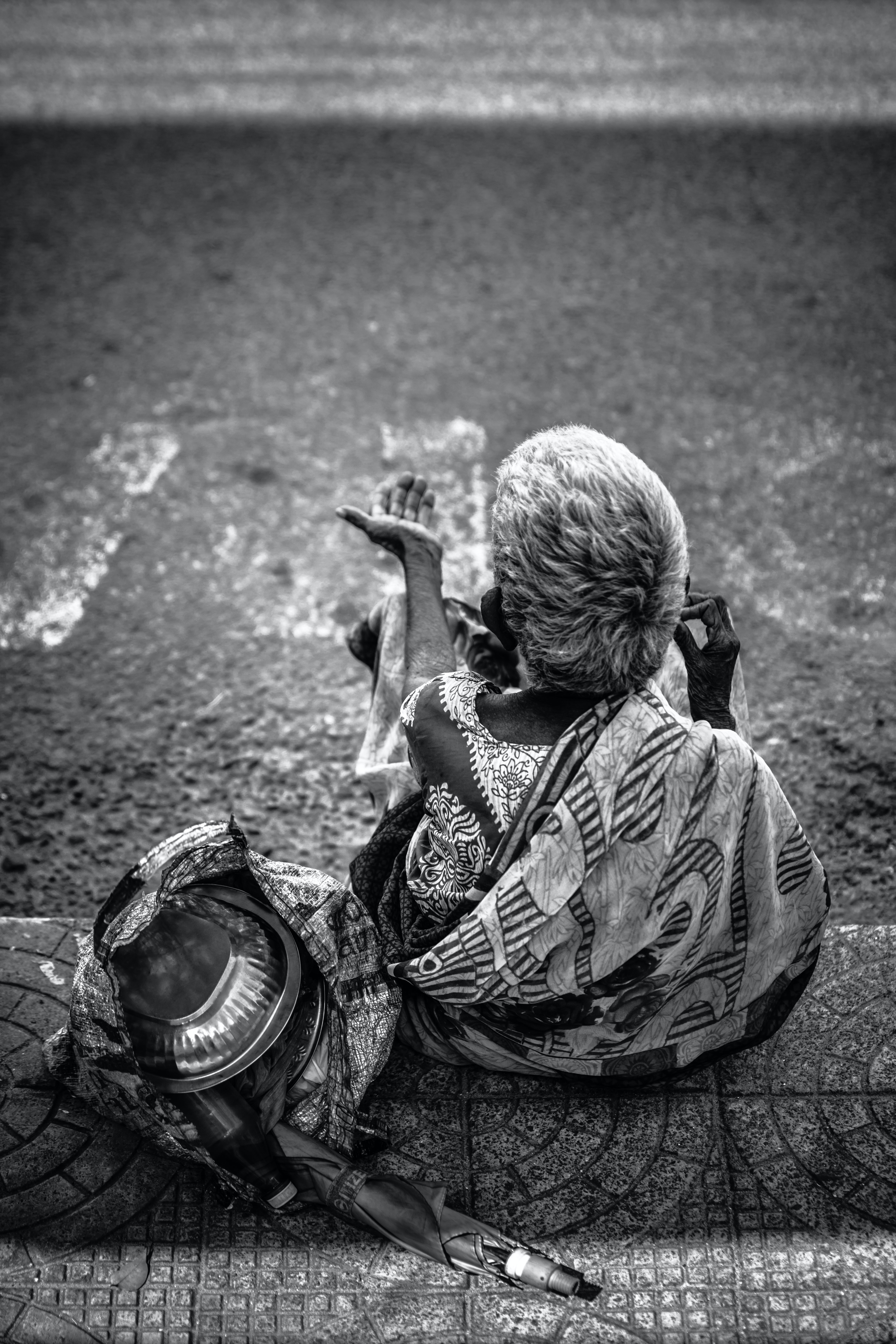 grayscale photography of person sitting near road