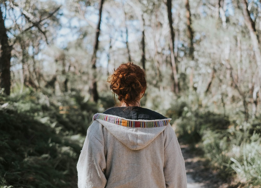 selective focus photography of woman wearing hoodie standing on ground surrounded with trees