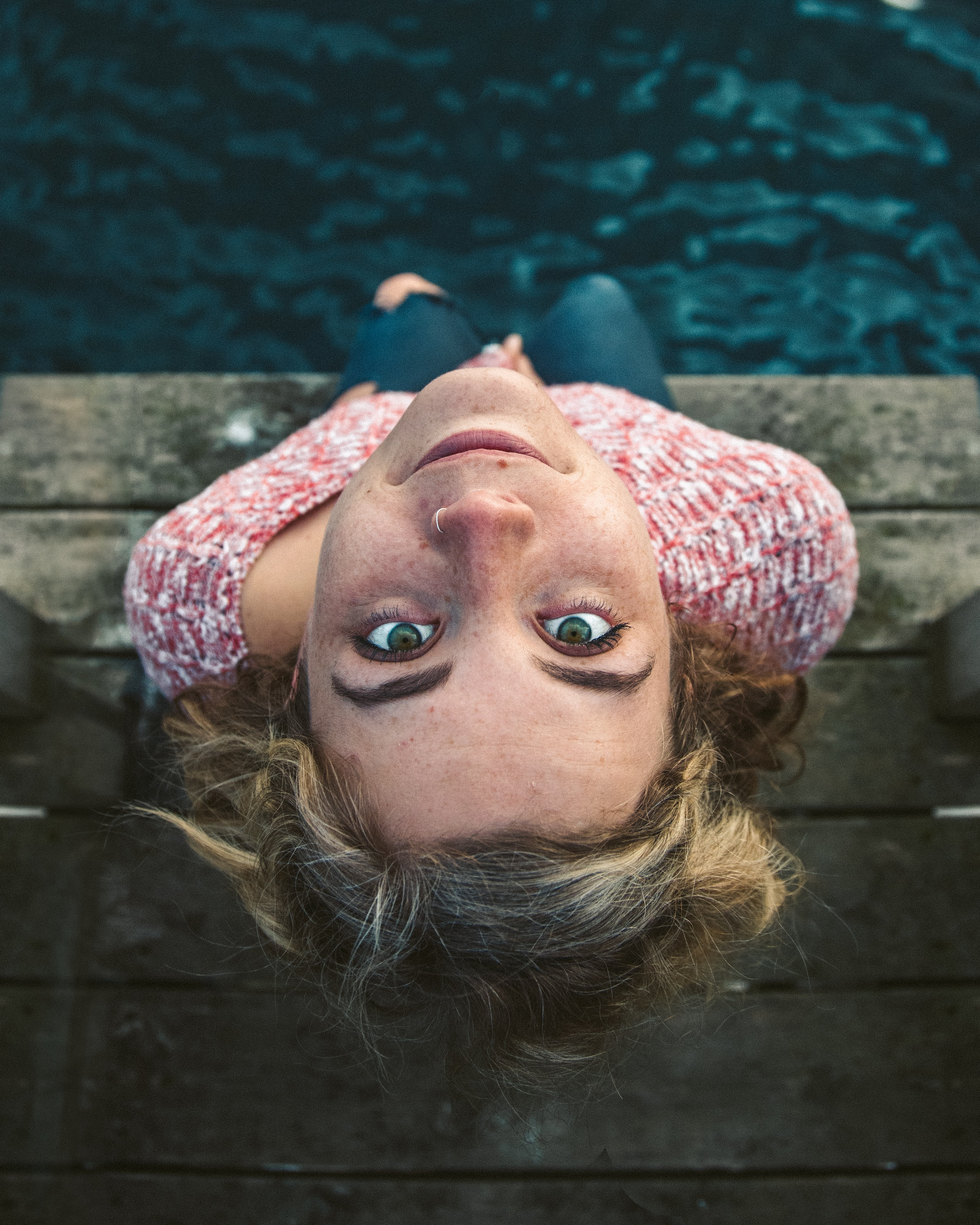 woman looking up while sitting on dock near water