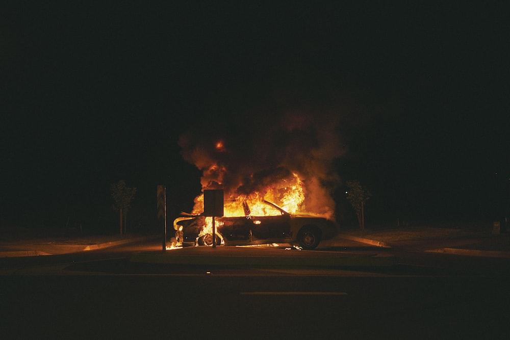 burning grey sedan near trees and signboard at night