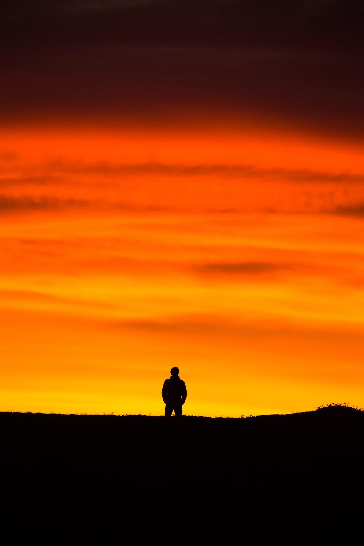 man standing at peak at golden hour