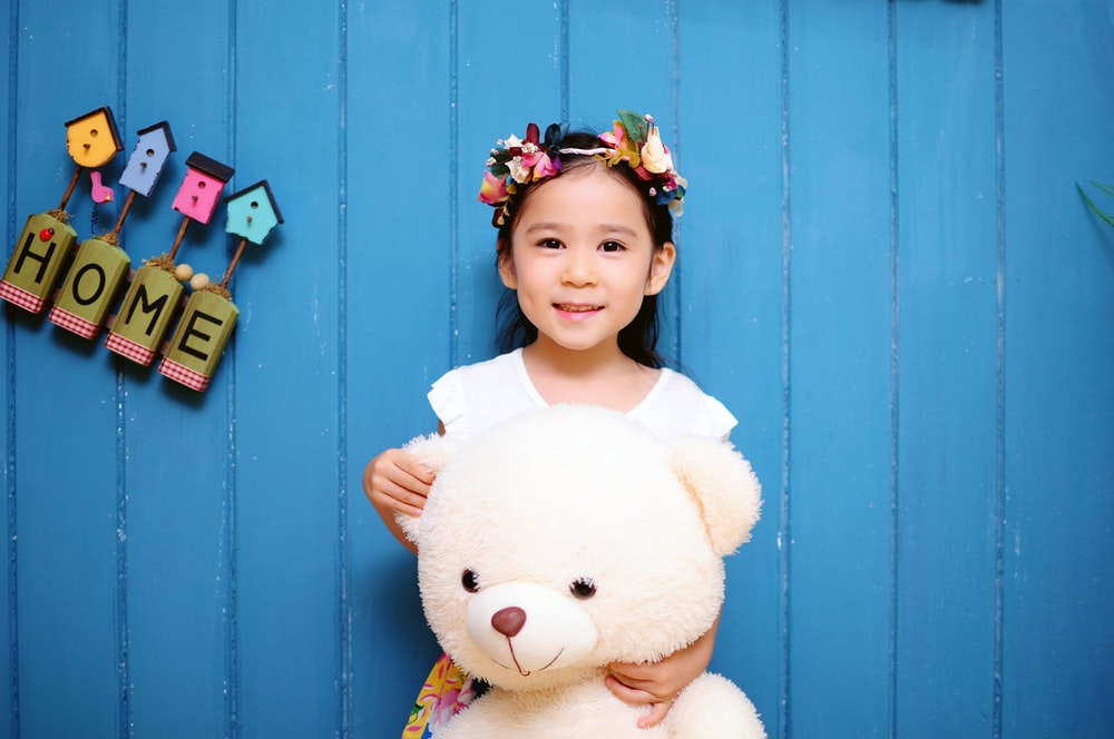 girl with white teddy bear stands with back on blue wooden wall