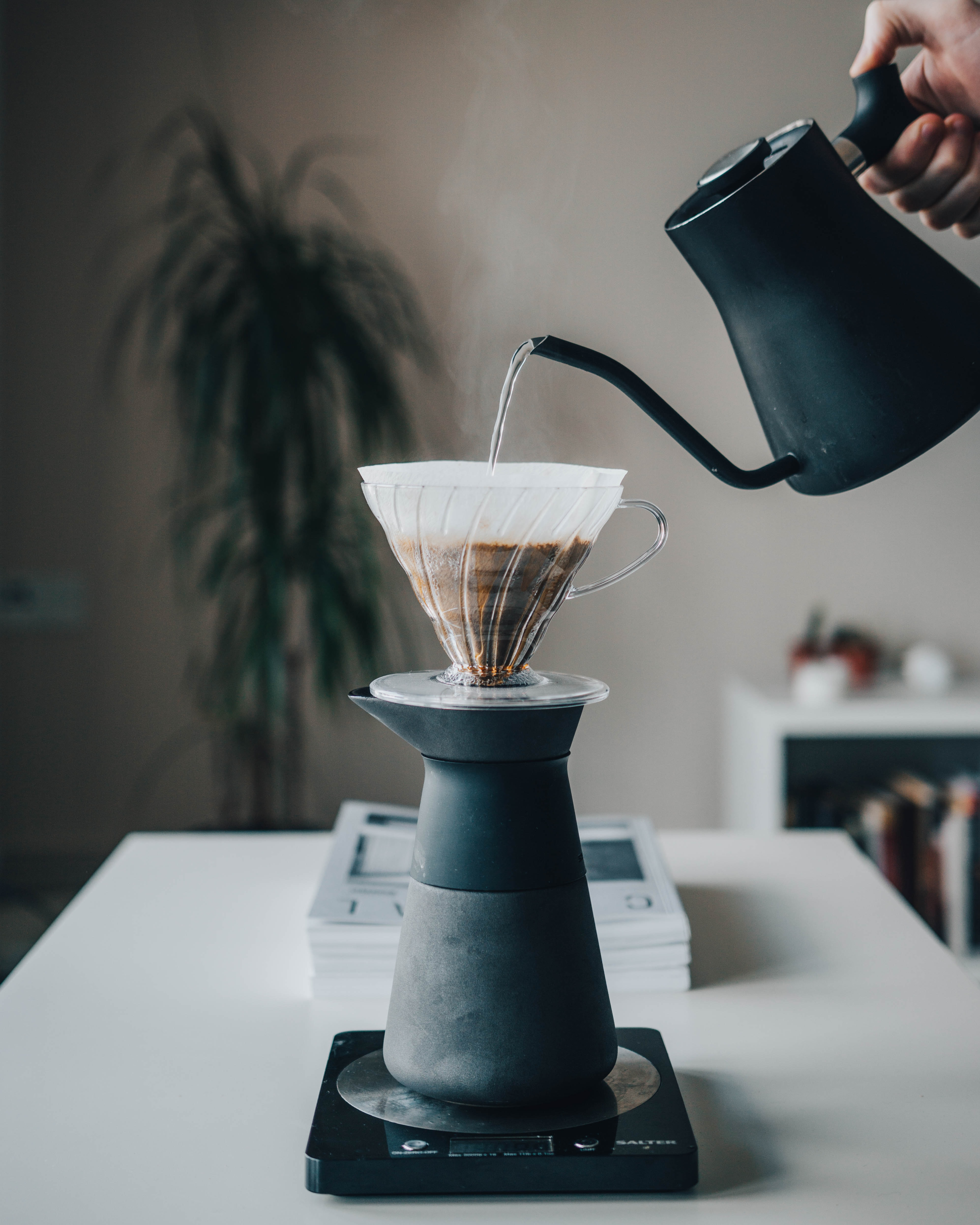 person pouring hot water on pour-over coffee maker