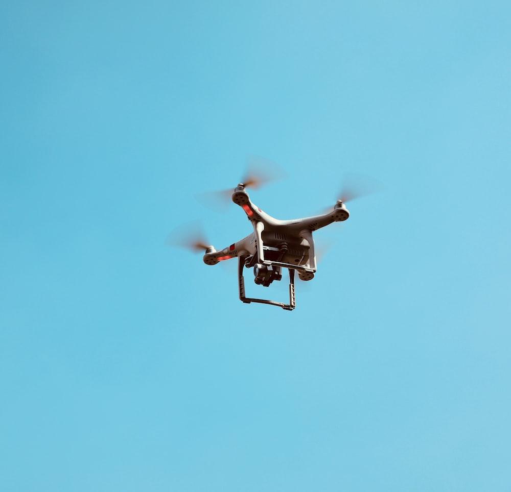white quadcopter drone in flight