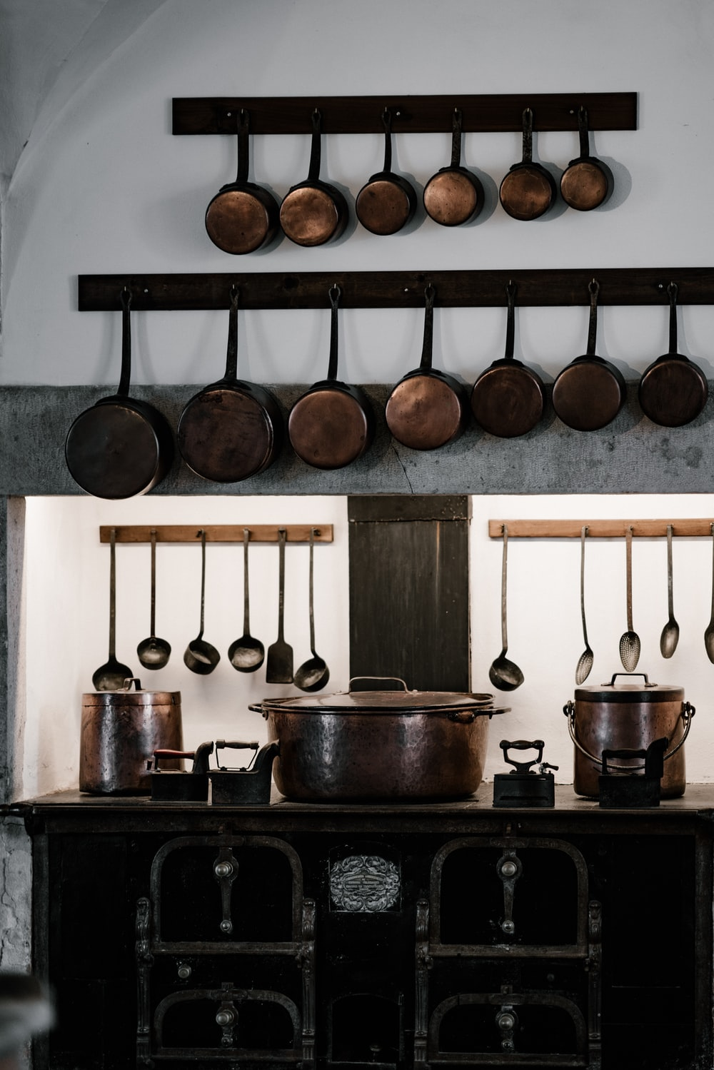 assorted cooking pots and pans hangs over black cast iron stove