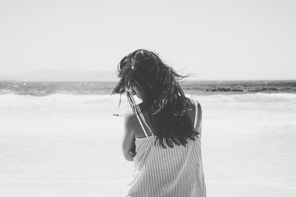 grayscale of woman in seashore