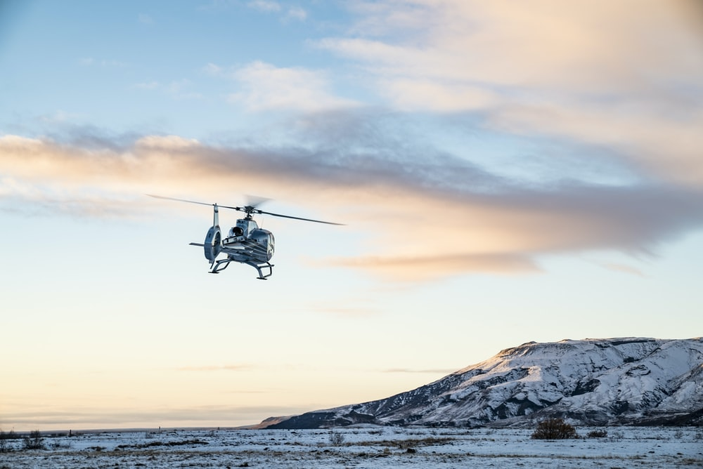 helicopter flies over snow covered tundra