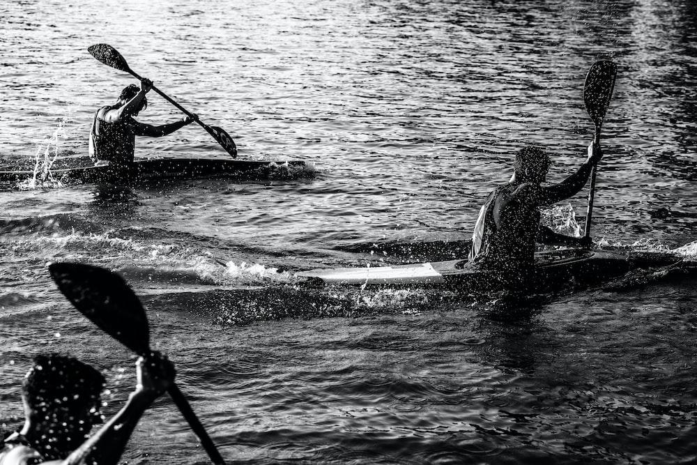 three men paddling kayak on water