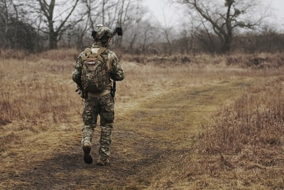 man walking on brown grass field military zoom background