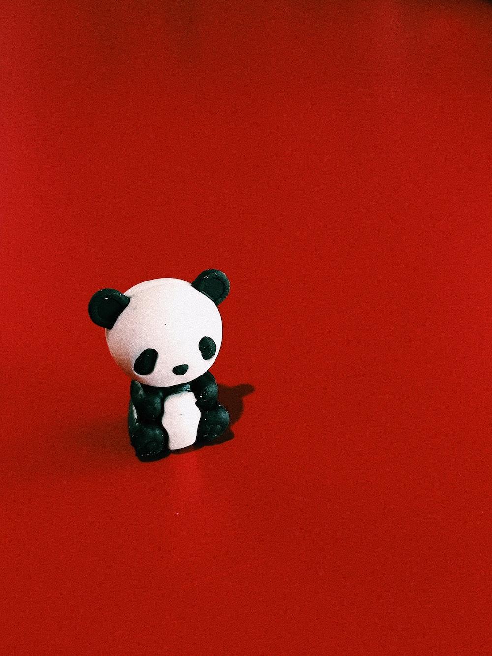 panda bear figurine sitting on red surface