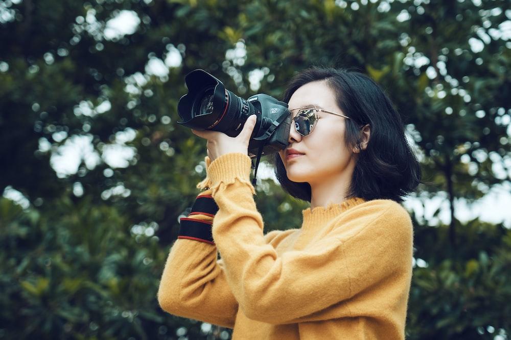 woman taking photo near tree