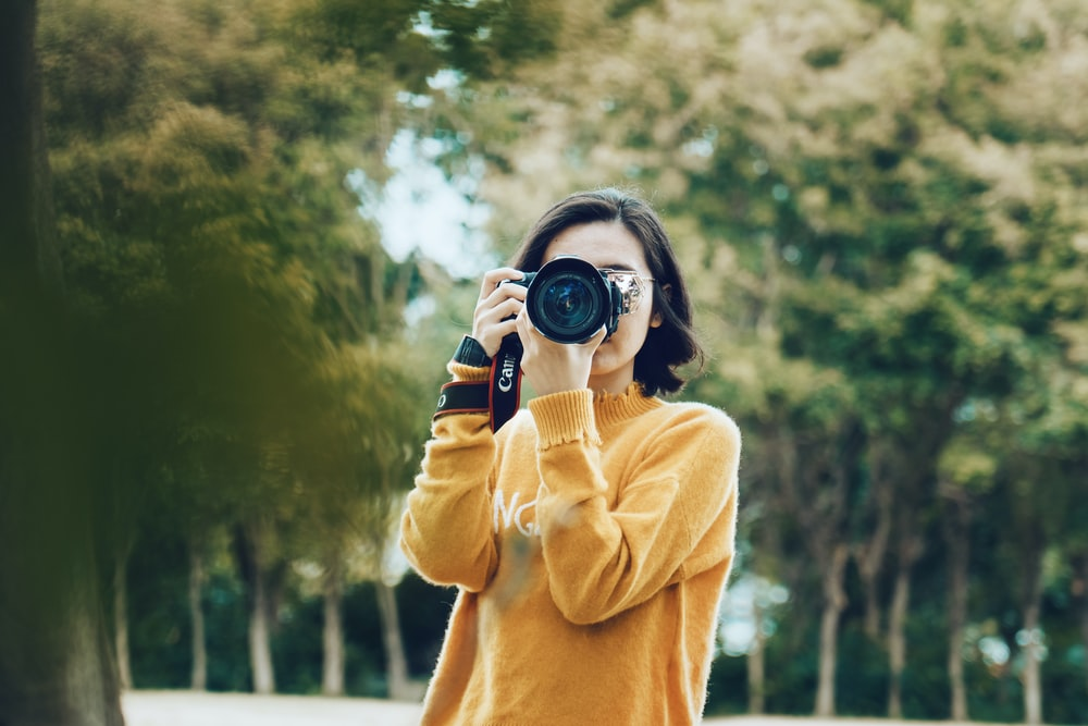 woman holding DSLR camera