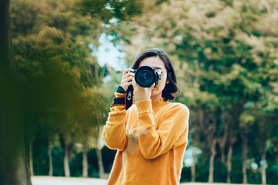 woman holding dslr camera camera zoom background
