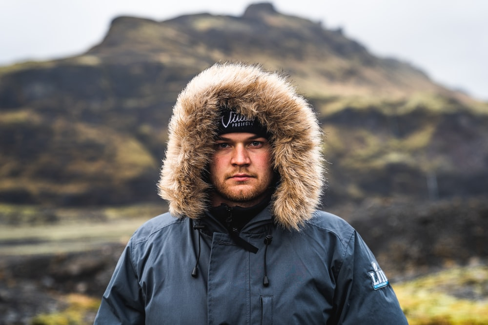 selective focus photography of man in blue parka coat