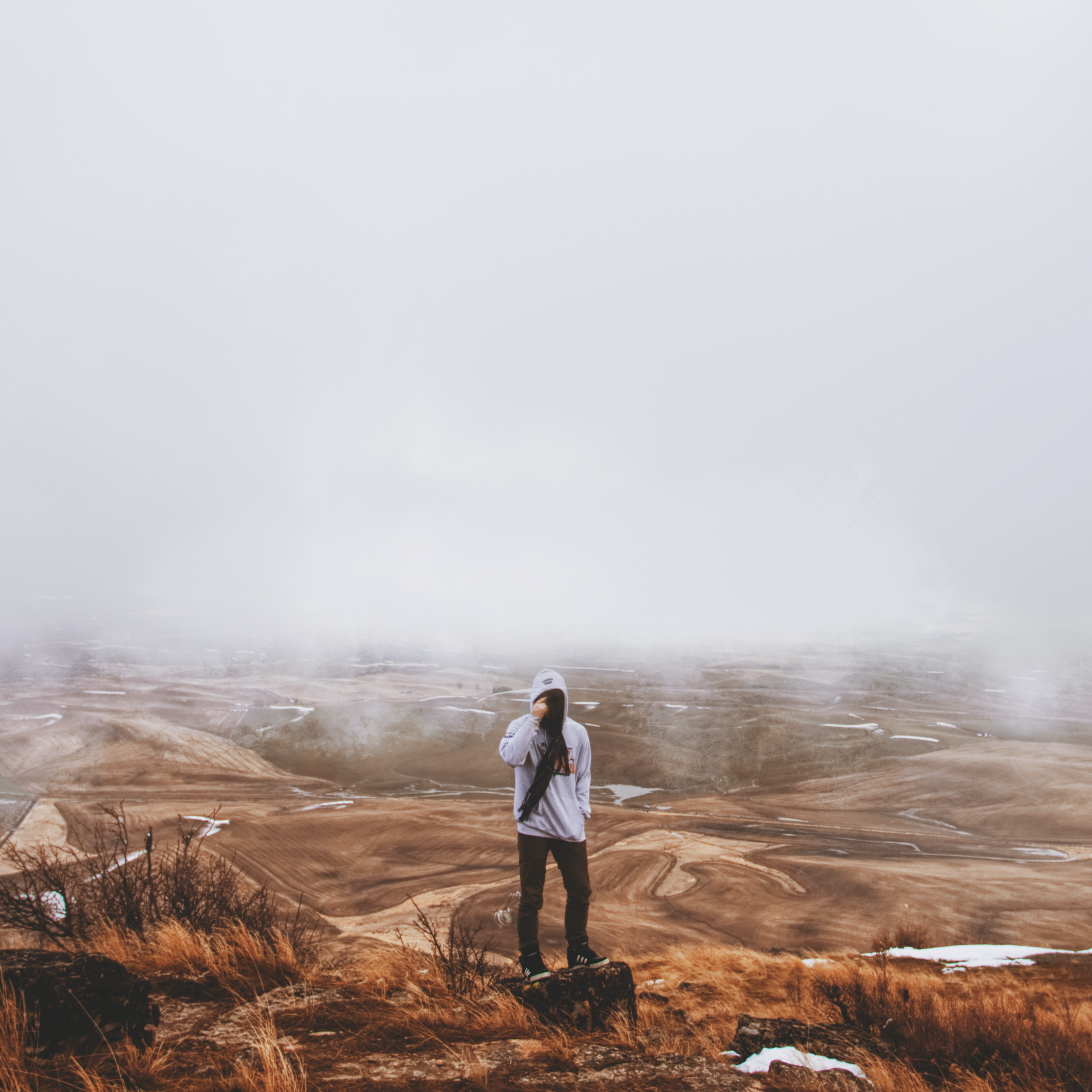 man standing on brown hill surrounded with mist