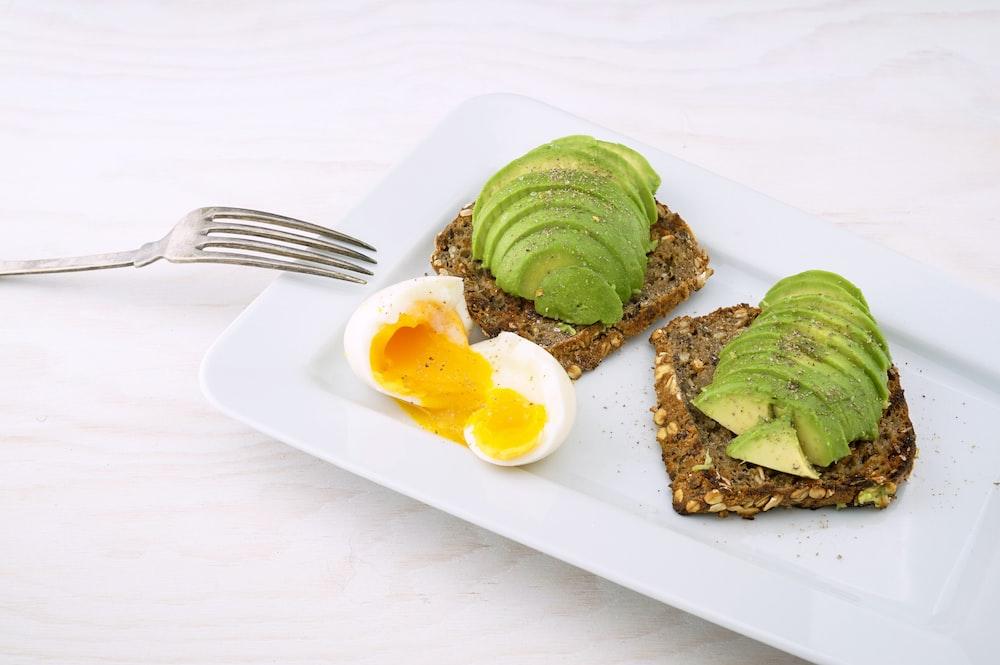 rectangular white platter of sliced food and eggs