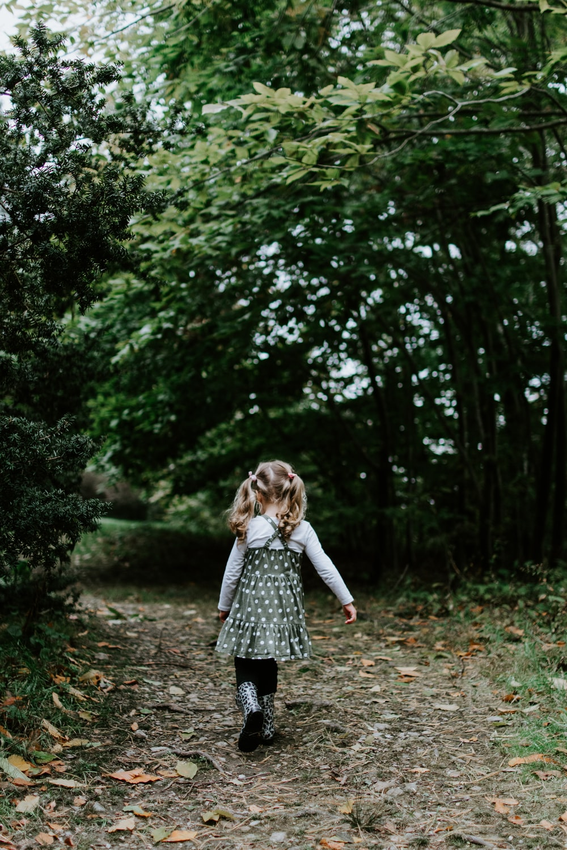 girl walking near green leafed trees