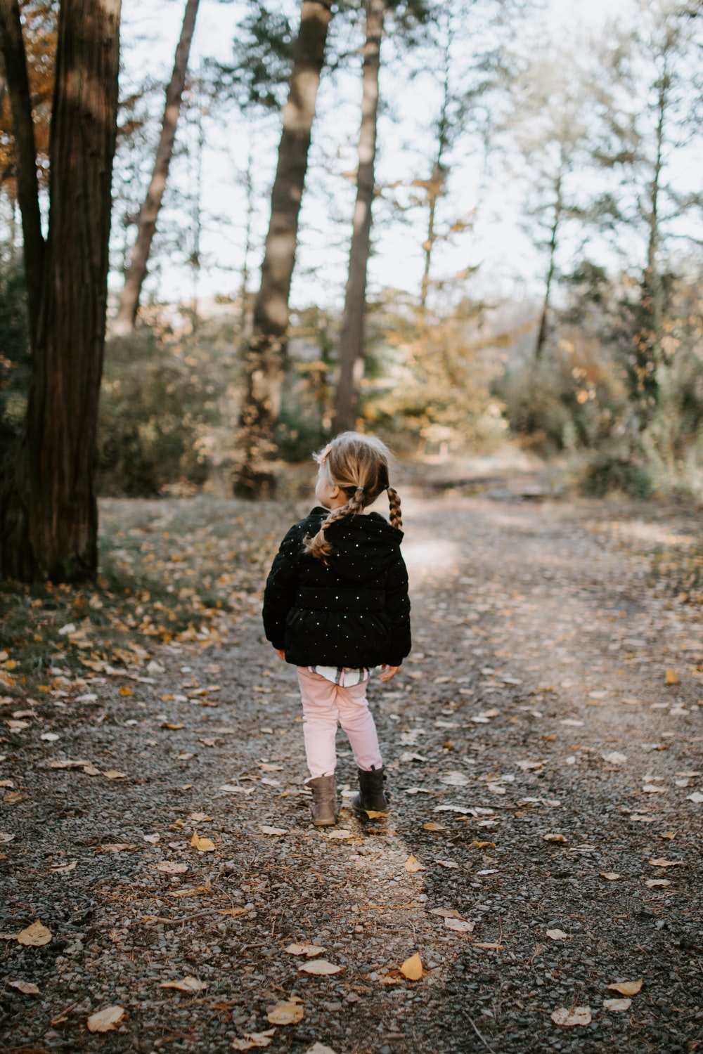girl in black jacket walking in the forest