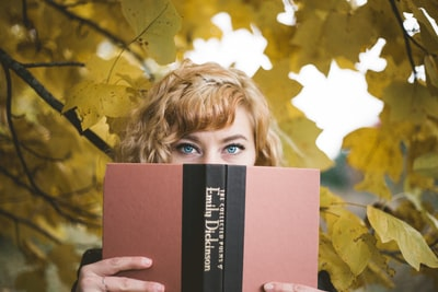 selective focus photography of woman holding emily dickinson book poem teams background