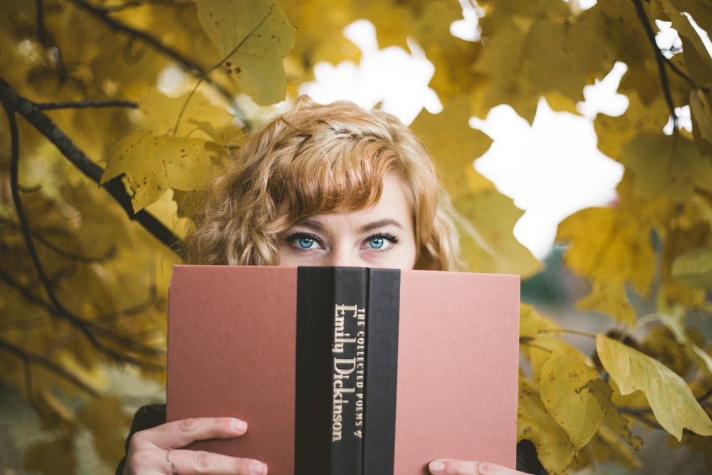 selective focus photography of woman holding Emily Dickinson book