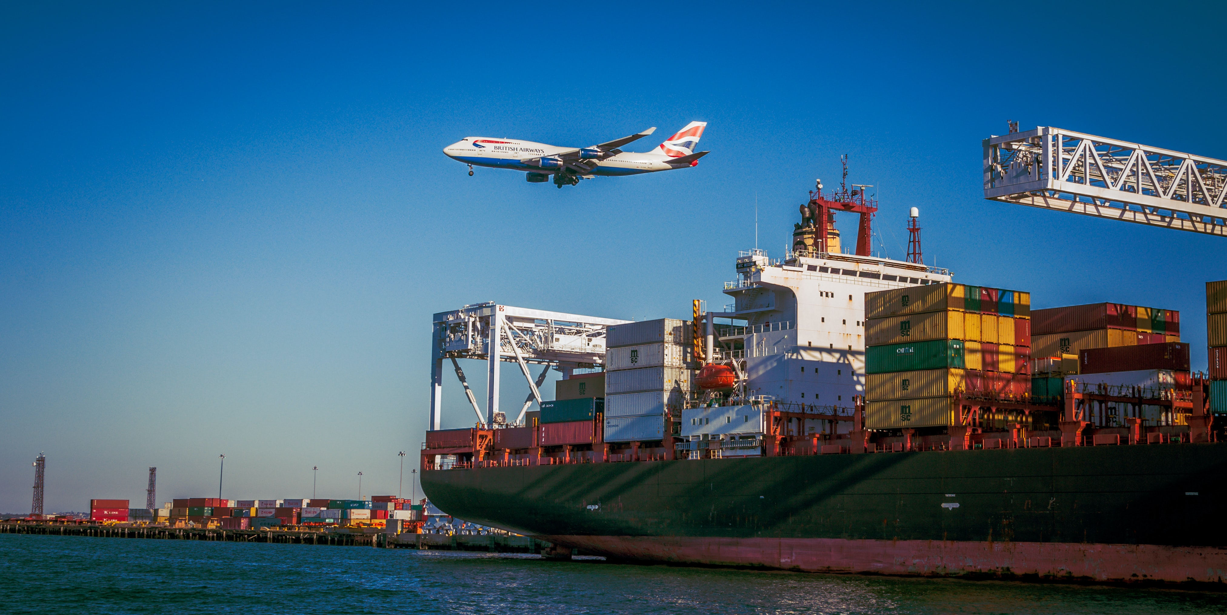 airplane on mid air passing by above cargo ship