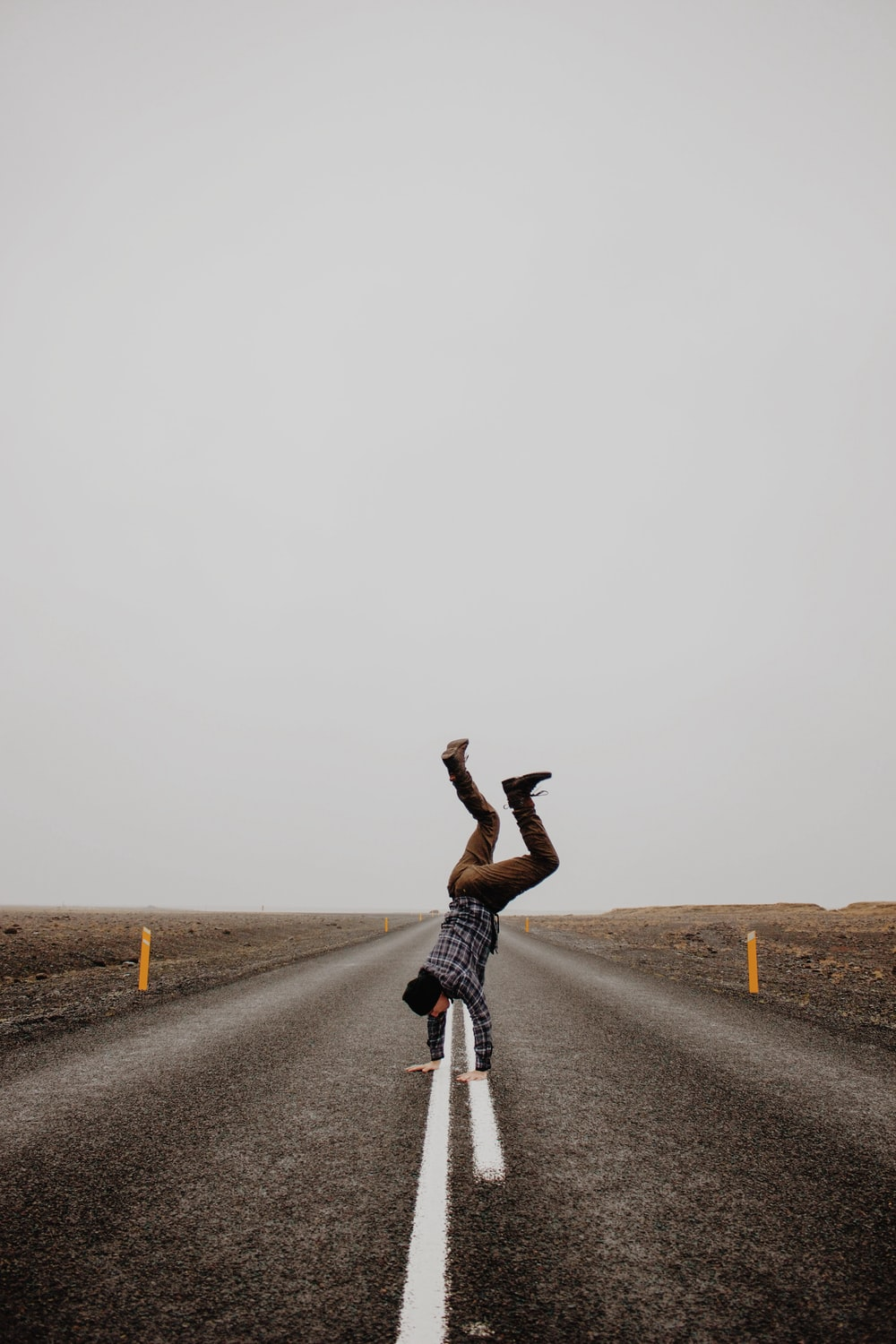 person hand standing on road during daytime