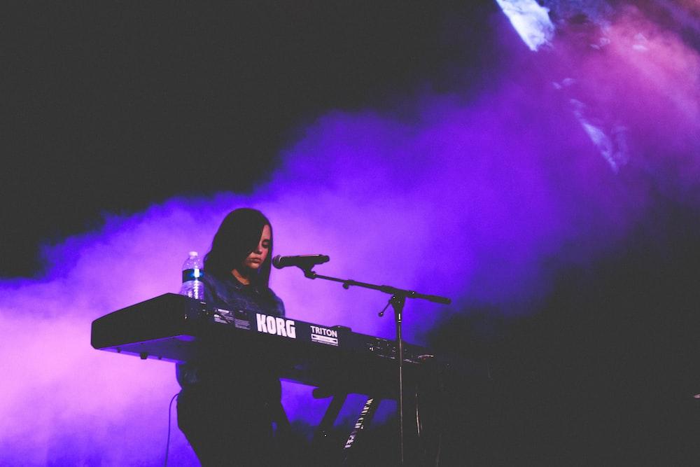 woman playing Korg electric keyboard