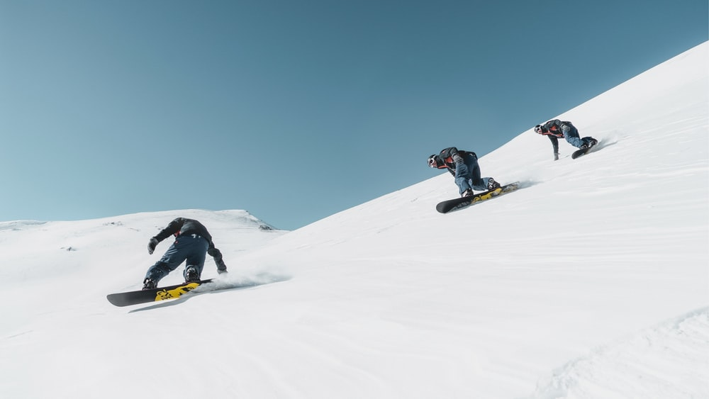 three person riding on snowboard