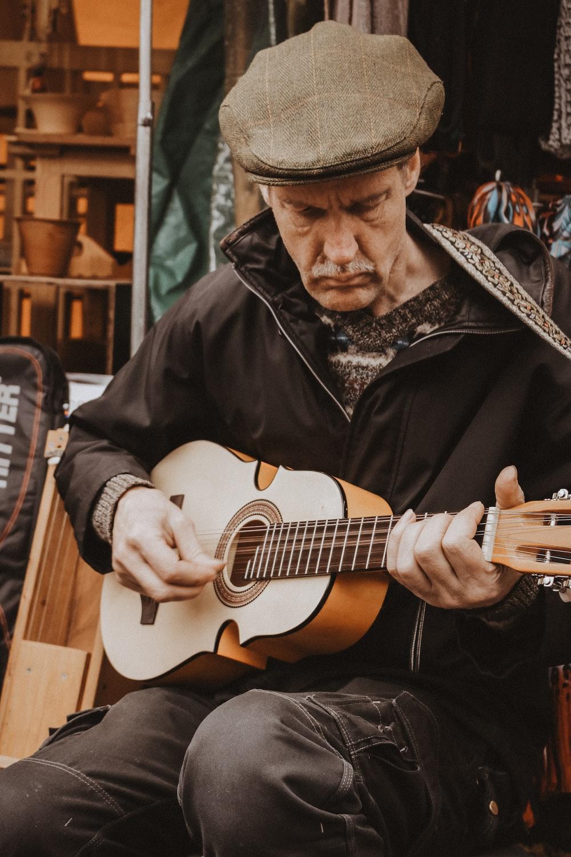 man wearing black jacket playing brown guitar