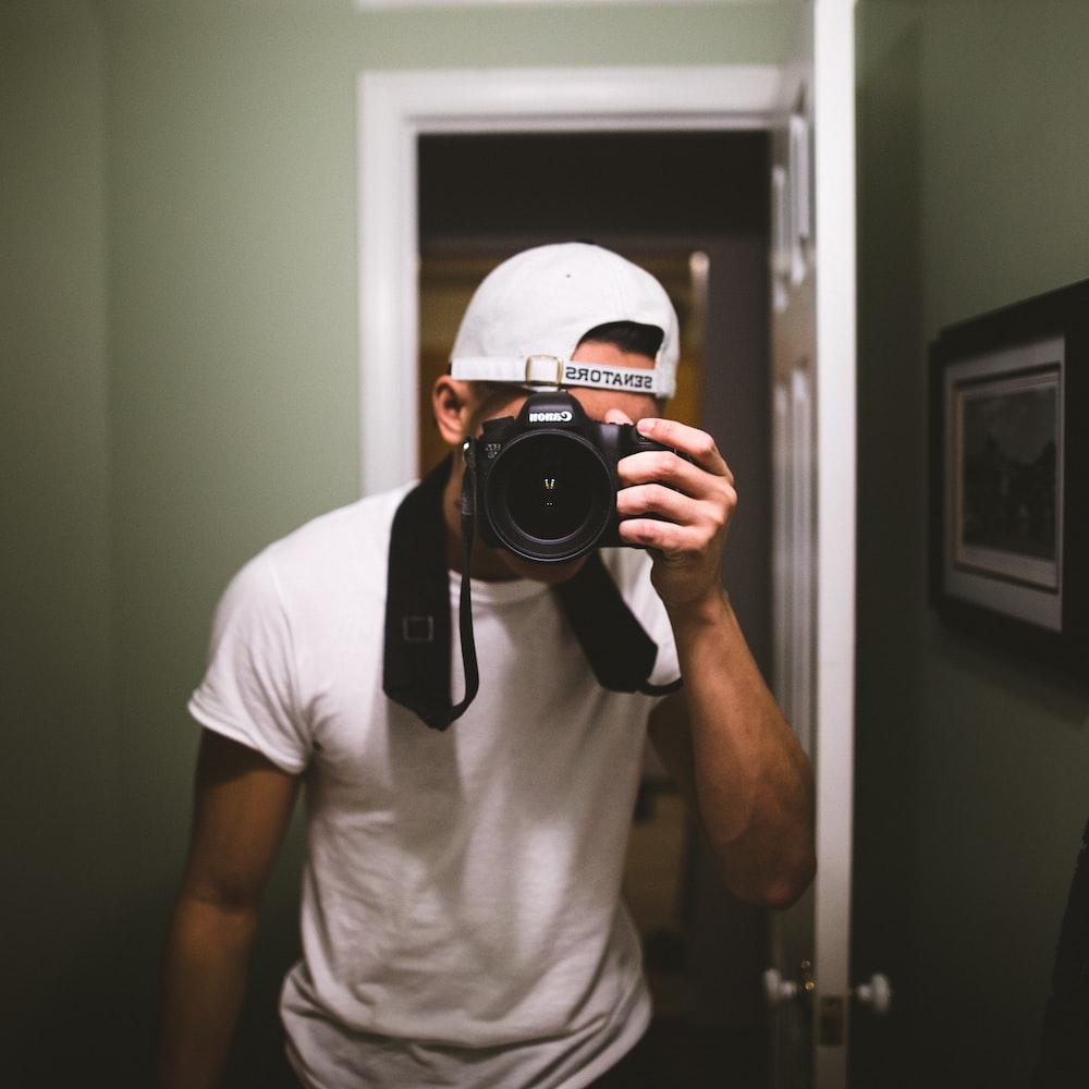 man taking a photo using black DSLR camera