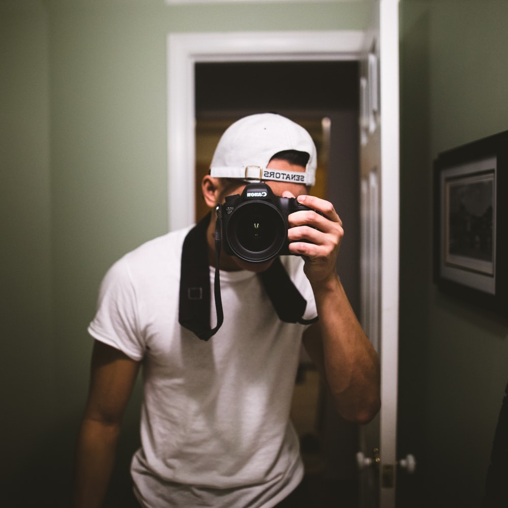 man taking a photo using black DSLR camera