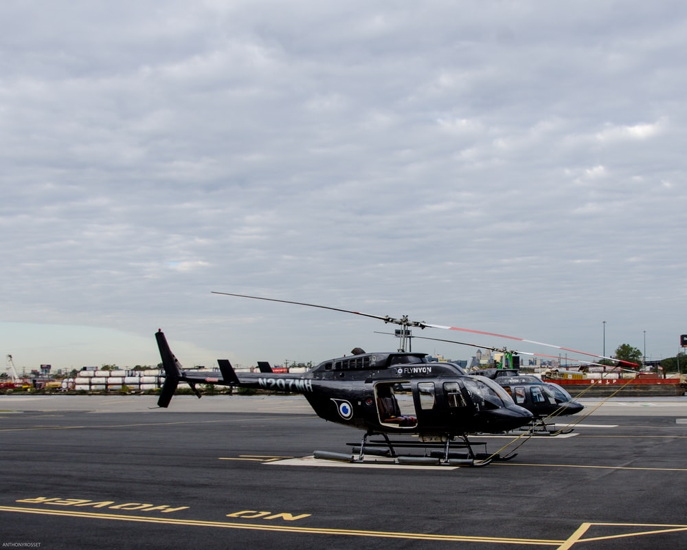 two black helicopters near on concrete pavement